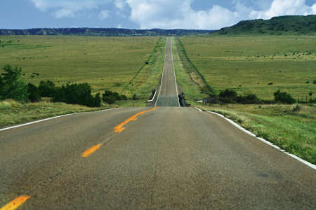open country: a long, open road disappearing in the distance into some low hills.  Green pastures and a blue lightly clouded sky hangs above.