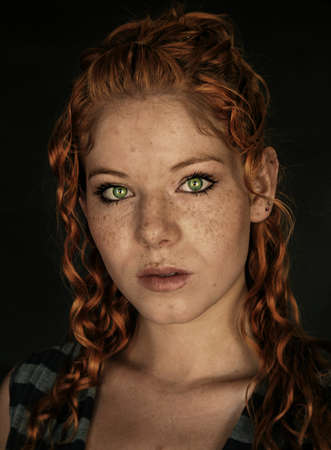 freckles: A freckled young woman  with copper red hair, and vibrant green eyes.