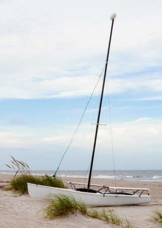 A catamaran boat sitting on the beach waiting for its next voyage.