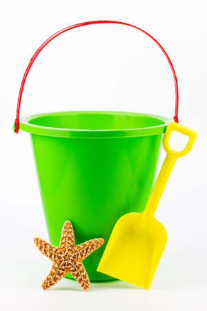 A green sand bucket with a yellow shovel and a starfish. photo