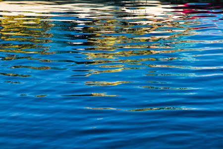 Colors reflected in rippling blue water  Stock Photo