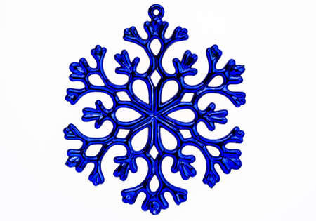 A blue plastic snowflake holiday ornament isolated on a white background  Stock Photo