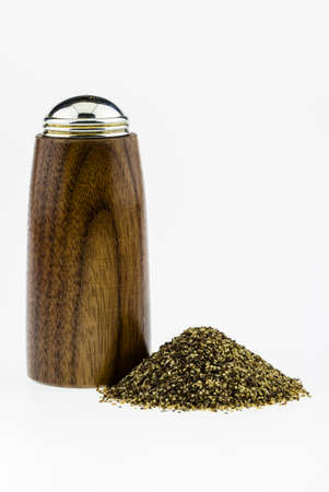Wood pepper shaker with black pepper in a pile next to it on a white background
