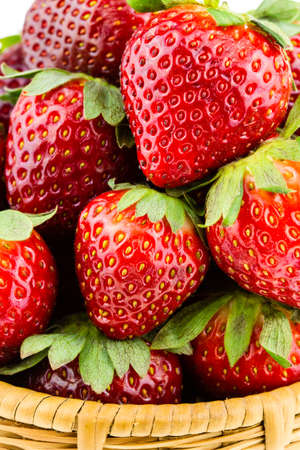 Ripe strawberries piled high in a wicker basket isolated against a white background  版權商用圖片