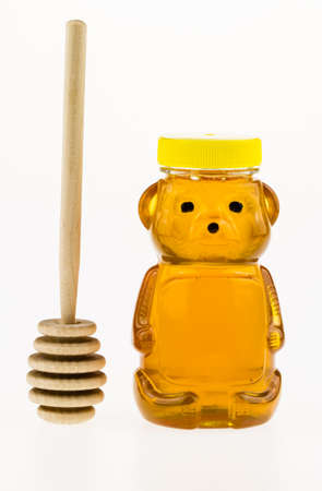 Sweet golden honey in a plastic bear shaped container with a wooden honey dipper  Stock Photo