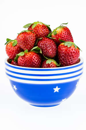 Ripe strawberries piled high in a blue and white bowl isolated against a white background