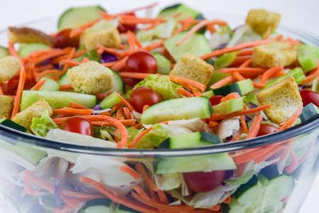 Fresh tossed garden salad set against a white background.