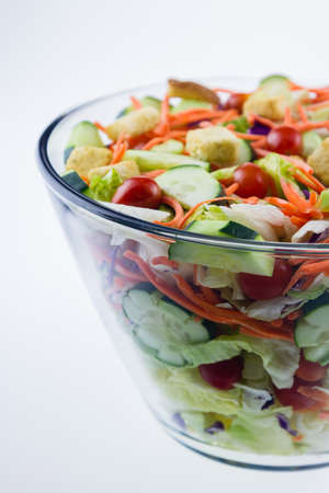 Fresh tossed garden salad in a glass bowl set against a white background.