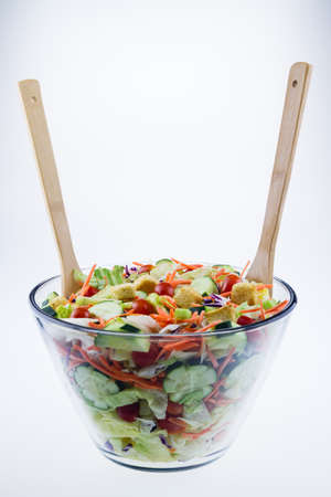 Fresh tossed garden salad in a glass bowl with wooden spoons set against a white background.