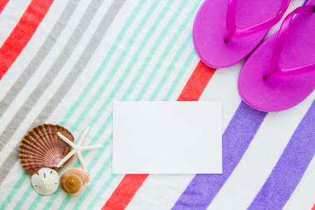 Beach scene with purple flip flops, shells, starfish, and a sand dollar on a striped beach towel with copy space.