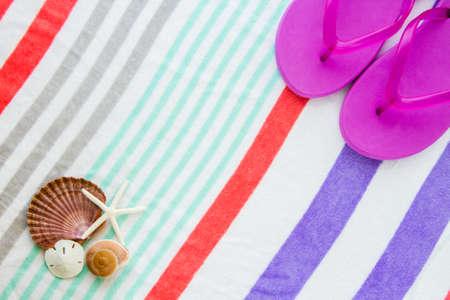 Beach scene with purple flip flops, shells, starfish, and a sand dollar on a striped beach towel.