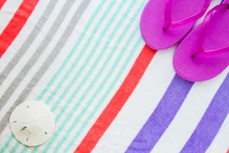 sand dollar: Escena de playa con chanclas de color p�rpura y un d�lar de arena en una toalla de playa con rayas. Foto de archivo
