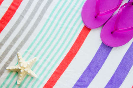 Beach scene with purple flip flops and a starfish on a striped beach towel.
