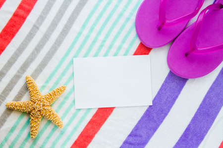 Beach scene with purple flip flops and a starfish on a striped beach towel with copy space. Stock Photo
