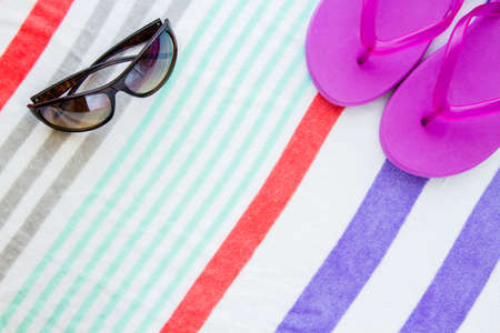Beach scene with purple flip flops and sunglasses on a striped beach towel. Stock Photo