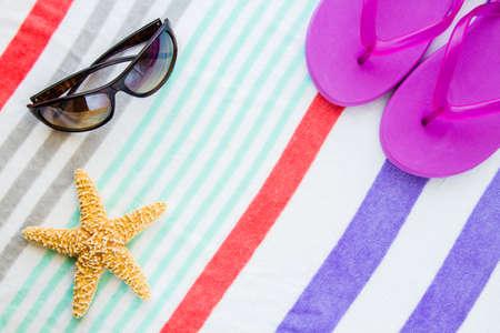 Beach scene with purple flip flops, sunglasses and a starfish on a striped beach towel.