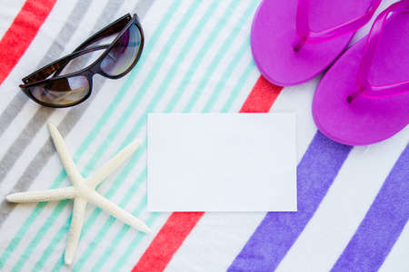 Beach scene with purple flip flops, a starfish, and sunglasses on a striped beach towel with copy space.