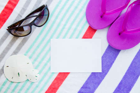 Beach scene with purple flip flops, sand dollars and sunglasses on a striped beach towel with copy space. Stock Photo