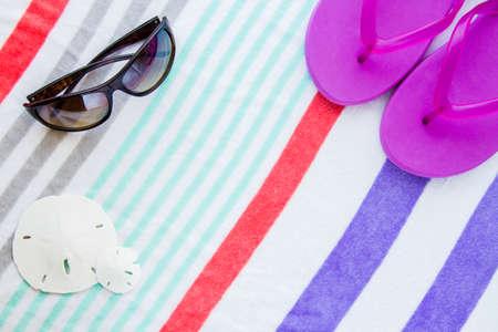 Beach scene with purple flip flops,sand dollars and sunglasses on a striped beach towel.
