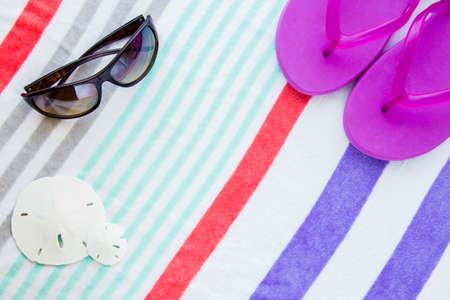 Beach scene with purple flip flops,sand dollars and sunglasses on a striped beach towel. photo