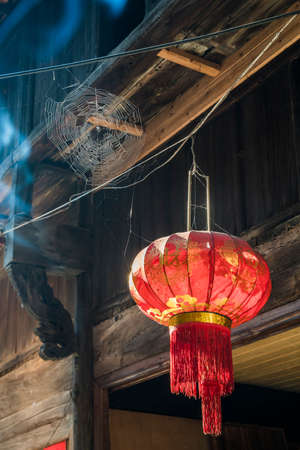 Chinese red lantern hanging from a roof .