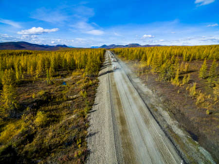 Aerial view of car driving through the forest on country road. Russia