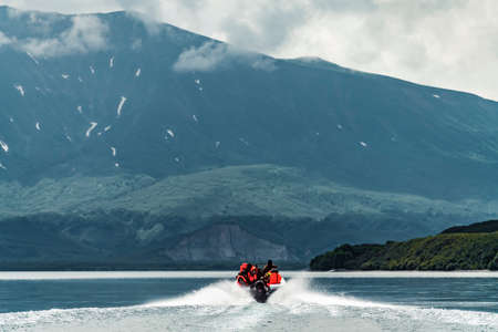 Photographer snapping pictures while on speedboat, Kuril lake, Kamchatka Peninsula, Russia