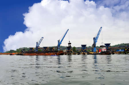 three crane unloading coal from barge to hopper