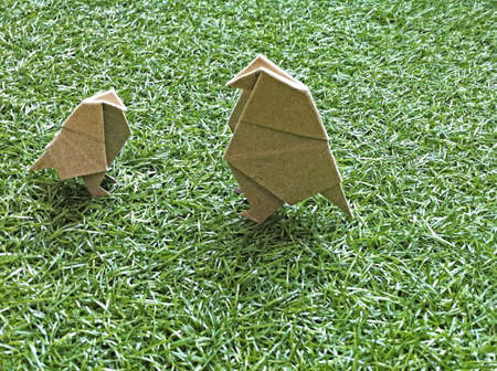 There are two origami birds on the grass. Stock Photo