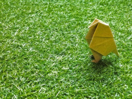There is a origami bird on the grass.