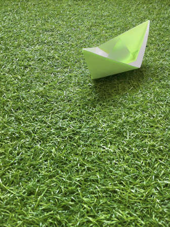 A paper boat on the grass.