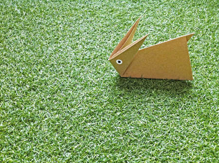A origami rabbit on the grass. Stock Photo