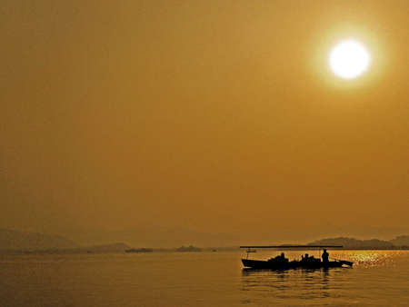 Serene silhouette of boat on golden water. Stock Photo