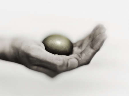 A hand hold the golden egg. Stock Photo