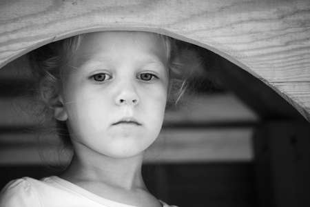 Little sad girl on the playground. Black and white series.