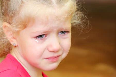 Little crying curly blonde girl portrait. Sad birthday.