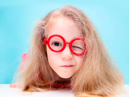 Funny little blonde girl with glasses looking at the camera.
