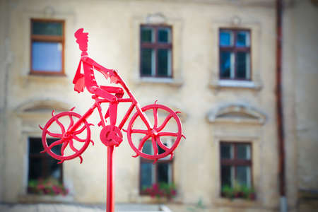 A man is riding a bicycle. Red metal figure. Stock fotó