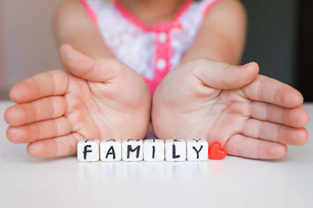 Little girl hold toy blocks with word Family. Protect your family concept. Word Family made of plastic blocks.