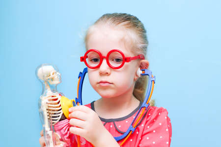 Little funny blonde girl with red glasses listen heart with stethoscope, stuck out her tongue. The skeleton of a man with insides. Early childhood development.