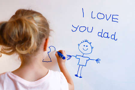 Little girl draws  family with marker on a white board. Happy fathers day card.
