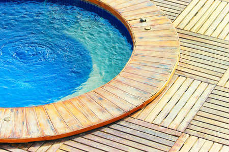 Outdoor jacuzzi pool with fresh blue water, wooden floor. Фото со стока