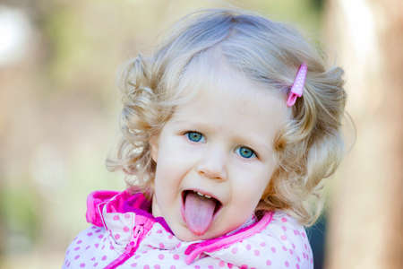 Little happy blonde curly hair girl showing tongue out.