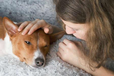 The girl hugs the basenji dog, toned.