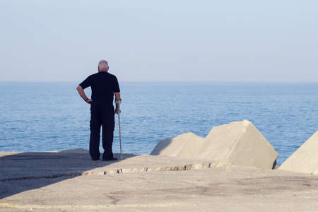 An elderly man with crutches stands on the beach and looks at the water