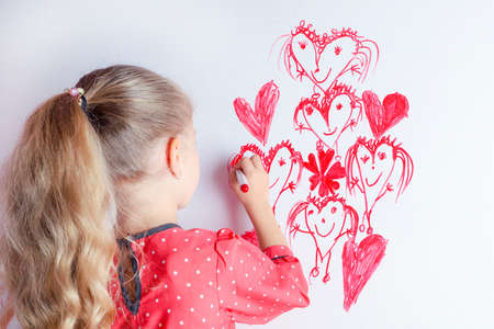 Little girl draws family with marker on a white board. Happy mothers day card.