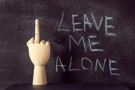 Wooden hand showing a middle finger standing on the white table on the black chalkboard background.