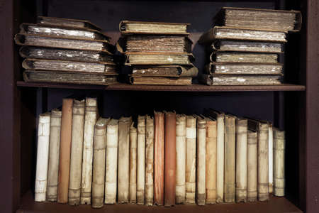 Ancient medieval books on the shelf in the bookcase. Medieval library.