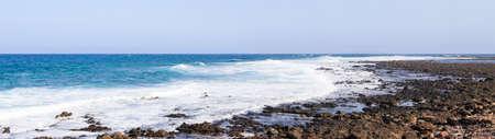 Panorama of the Spanish island of Fuerteventura, stones, rocks and the ocean.