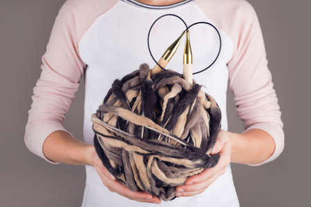Young woman holding a big yarn of thick thread in her hands.